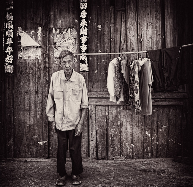 Portrait of man with clothes drying, Old Xing Ping Town, Guilin, China