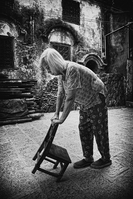 Ederly lady using chair as walking frame, Guilin, China.
